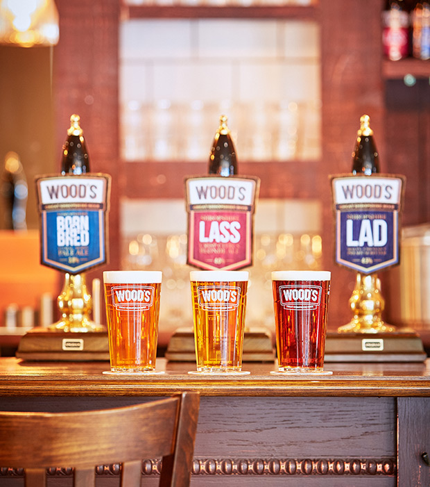 beer pumps on the plough inn bar showing woods brewery shropshire lad, lass and born n bred
