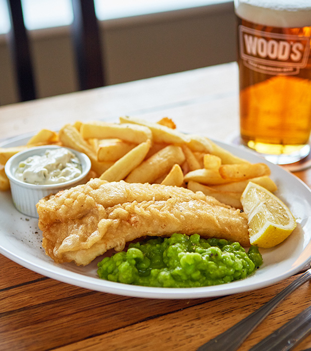 Juicy Shropshire Lass battered cod served at the brewery tap with chips mushy peas tartare sauce a wedge of fresh lemon and of course a pint of woods beer